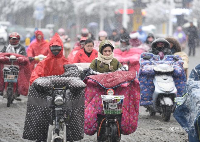 Những người phụ nữ Trung Quốc trùm chăn kín ra đường trong thời tiết lạnh giá.