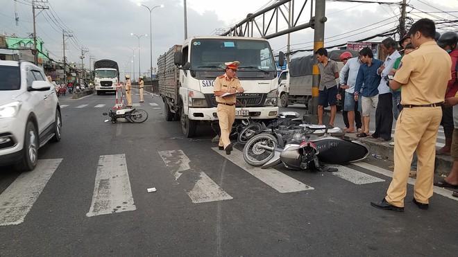 Ôtô tải tông hàng loạt xe máy giữa giao lộ Sài Gòn, SH cuốn vào gầm, nhiều người bị thương - Ảnh 1.