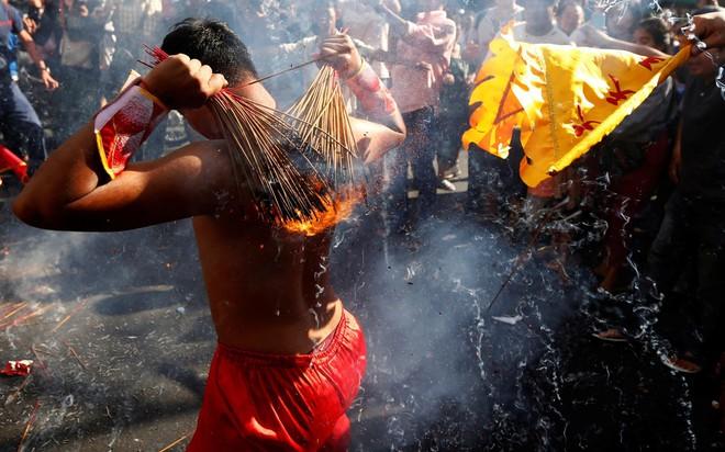 24h qua ảnh: Người Campuchia đốt hương trên lưng trần mừng năm mới - ảnh 3