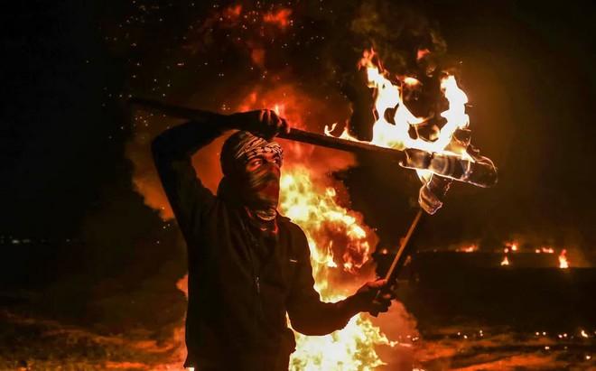 24h qua ảnh: Người Campuchia đốt hương trên lưng trần mừng năm mới - ảnh 9