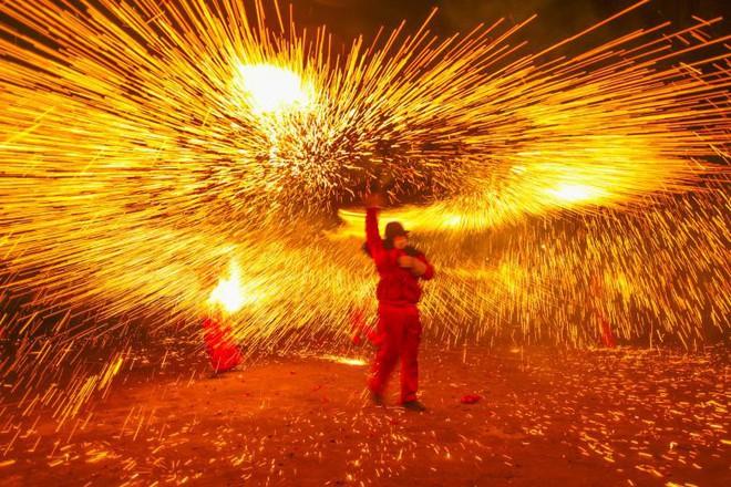 24h qua ảnh: Người Campuchia đốt hương trên lưng trần mừng năm mới - ảnh 1