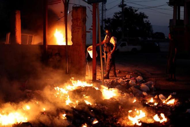 24h qua ảnh: Người Campuchia đốt hương trên lưng trần mừng năm mới - ảnh 5