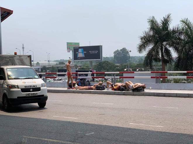 Nằm tắm nắng 40 độ ở sảnh sân bay Nội Bài, nhóm Tây ba lô gây tranh cãi trên MXH - Ảnh 1.