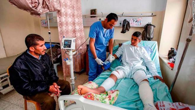 Cảnh tượng kinh hoàng: 4 lính Israel vây bắt, nã đạn vào thiếu niên Palestine bị bịt mắt, còng tay - Ảnh 3.