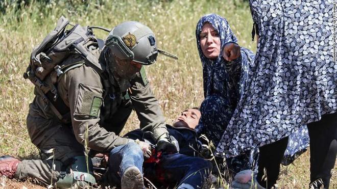 Cảnh tượng kinh hoàng: 4 lính Israel vây bắt, nã đạn vào thiếu niên Palestine bị bịt mắt, còng tay - Ảnh 2.