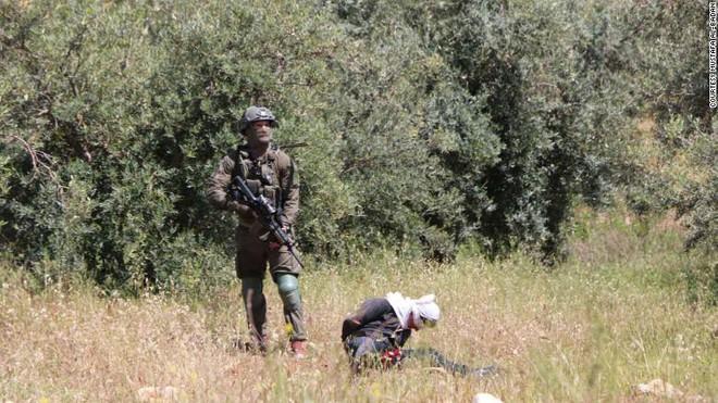 Cảnh tượng kinh hoàng: 4 lính Israel vây bắt, nã đạn vào thiếu niên Palestine bị bịt mắt, còng tay - Ảnh 1.