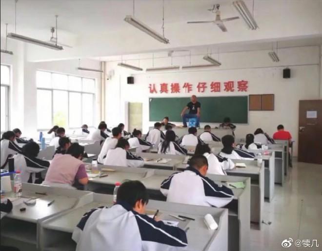 Quá mệt mỏi với những mánh khoé thi cử, thầy giáo bê hẳn ghế lên bàn ngồi coi thi như một vị thần khiến học trò sợ xanh mặt - Ảnh 1.