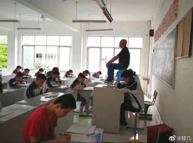Quá mệt mỏi với những mánh khoé thi cử, thầy giáo bê hẳn ghế lên bàn ngồi coi thi như một vị thần khiến học trò sợ xanh mặt - Ảnh 2.