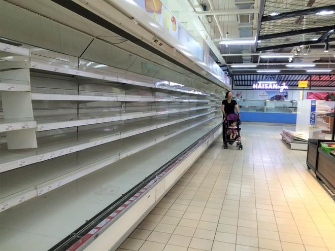 Siêu thị Auchan vắng vẻ, lặng lẽ tháo các kệ hàng sau bão giảm giá - Ảnh 2.