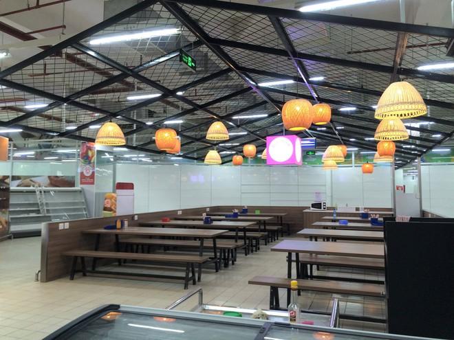Siêu thị Auchan vắng vẻ, lặng lẽ tháo các kệ hàng sau bão giảm giá - Ảnh 4.