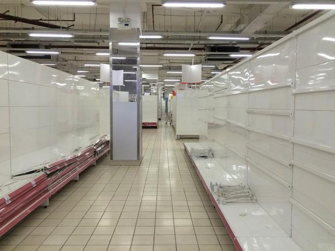 Siêu thị Auchan vắng vẻ, lặng lẽ tháo các kệ hàng sau bão giảm giá - Ảnh 9.