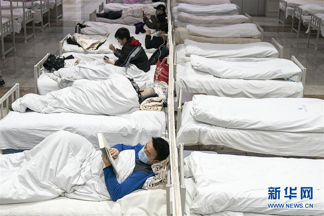 Bệnh viện cabin vuông 1.600 giường đầu tiên ở Vũ Hán đi vào hoạt động, bệnh nhân bình thản đọc sách - Ảnh 9.