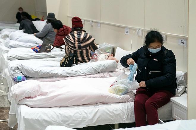 Bệnh viện cabin vuông 1.600 giường đầu tiên ở Vũ Hán đi vào hoạt động, bệnh nhân bình thản đọc sách - Ảnh 10.