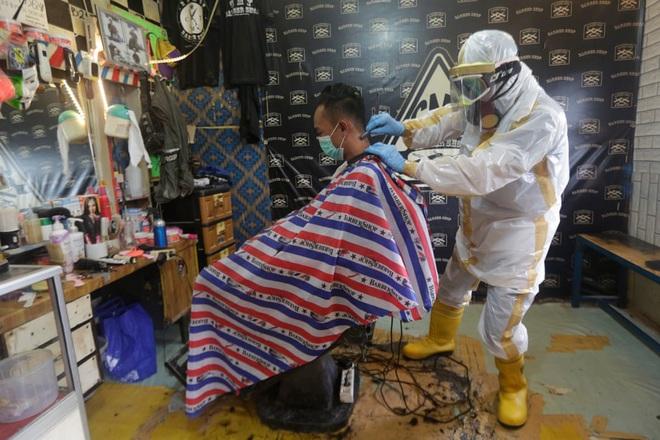 24h qua ảnh: Thợ cắt tóc mặc trang phục bảo hộ kín mít khi phục vụ khách - Ảnh 3.