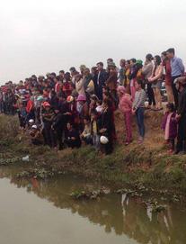Người dân đổ xô đến xem một con cá nổi dưới mương ngày Tết