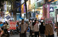 Nhiều nhân viên cửa hàng thời trang ở Sài Gòn cầm bảng giá tràn ra đường chào mời khách dịp cận Tết