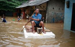 24h qua ảnh: Người Indonesia vượt nước lũ bằng bè tự chế