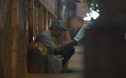 Có một cụ ông nhặt ve chai say sưa đọc báo dưới ánh đèn trên phố Sài Gòn
