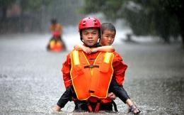 24h qua ảnh: Nhân viên cứu hộ cõng em bé trong mưa lũ