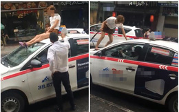 """Người phụ nữ trèo lên nóc xe taxi """"ăn vạ"""" giữa phố Hà Nội"""
