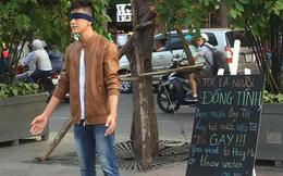 """Chàng trai gây chú ý khi bịt mắt giữa phố đi bộ cùng tấm bảng """"Tôi là gay, bạn sẽ ôm tôi hay tạt nước?"""""""