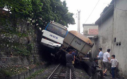 """Tàu hỏa chèn xe khách chở công nhân """"lơ lửng"""" trên sườn đồi"""