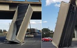 Một chiếc thùng container nằm dựng đứng giữa đường mà không ai hiểu sao tài xế làm được như vậy