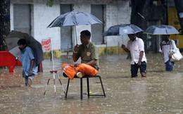 """24h qua ảnh: Công nhân đô thị """"bảo vệ"""" nắp hố ga giữa mưa, lụt ở Ấn Độ"""