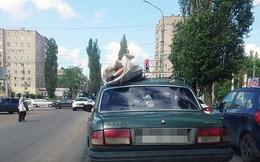 Xác chết được chất lên nóc ô tô chạy trên đường phố