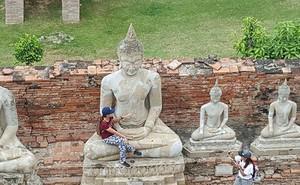 """Nữ du khách bị """"ném đá"""" vì ngồi vào lòng tượng Phật"""