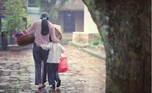 Mẹ bán hương dạo dùng nón lá che mưa cho con - bức ảnh giản dị nhưng mang sức mạnh to lớn, khiến dân mạng xúc động