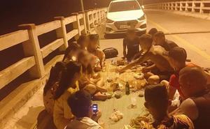 Hình ảnh nhóm thanh niên đỗ ô tô chặn đường, trải chiếu ngồi nhậu trên cầu gây bức xúc