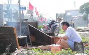 Người Hà Nội bắc bếp luộc bánh chưng cạnh đường ray tàu hỏa chạy qua