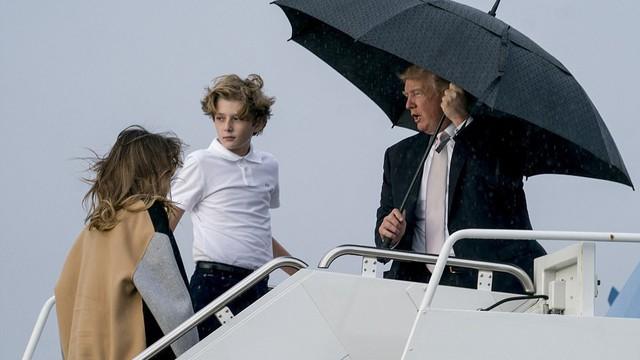 Tổng thống Trump che ô một mình, phu nhân và con trai đầu trần hứng gió mưa