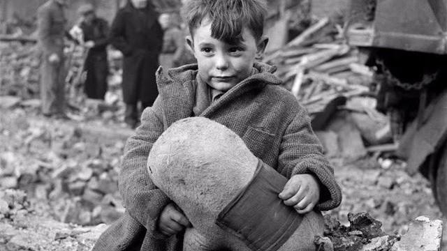 Gương mặt đầy vẻ thách thức của chú bé đang ngồi ôm chặt con thú bông bên cạnh đống đổ nát và bi kịch khiến ai cũng xót xa