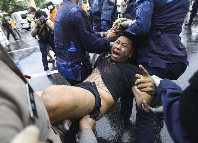 Nhà vua Thái Lan vẫy chào người dân dưới mưa dù biểu tình lan rộng - Ảnh 1.