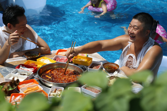 Thời tiết nóng nực, người dân Trung Quốc tràn xuống bể bơi ngồi ăn lẩu siêu cay - Ảnh 1.