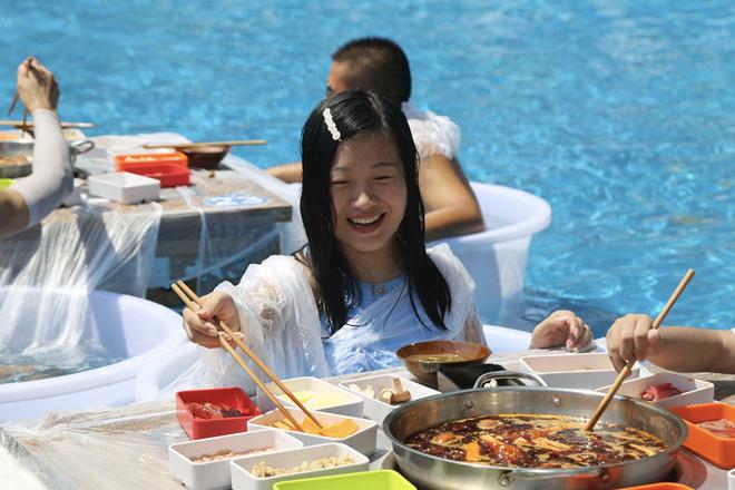 Thời tiết nóng nực, người dân Trung Quốc tràn xuống bể bơi ngồi ăn lẩu siêu cay - Ảnh 2.