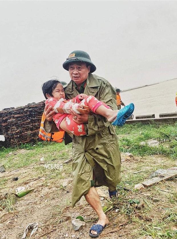 Khoảnh khắc chiến sĩ công an bế bé gái gãy tay vội vã lên ô tô tới bệnh viện trong cơn mưa lũ Quảng Bình gây xúc động - Ảnh 1.