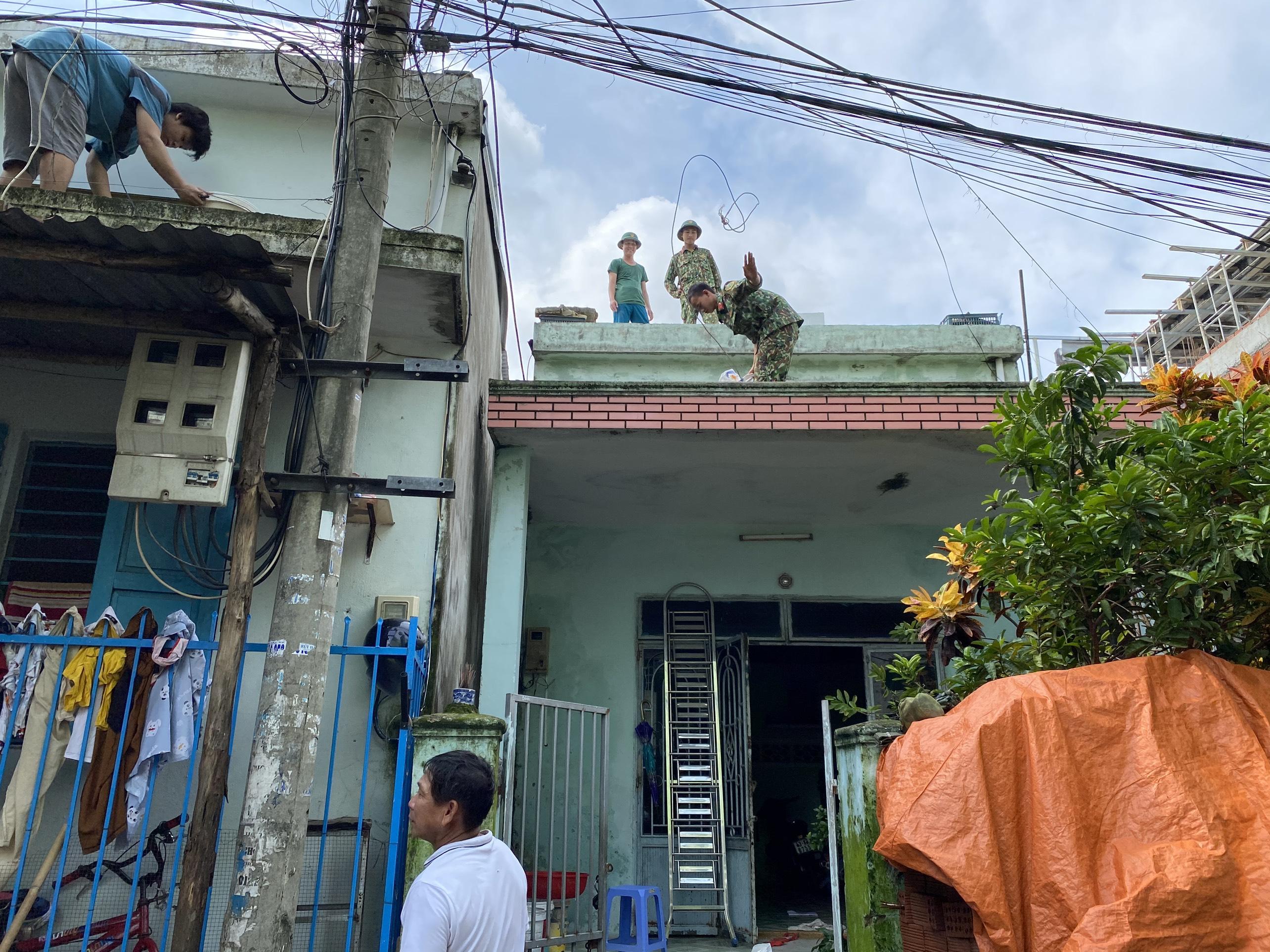 [Ảnh] Xe tải cẩu chở thuyền đến nơi an toàn, công an, bộ đội giúp người Đà Nẵng chằng chống nhà cửa đón bão số 9 - Ảnh 10.