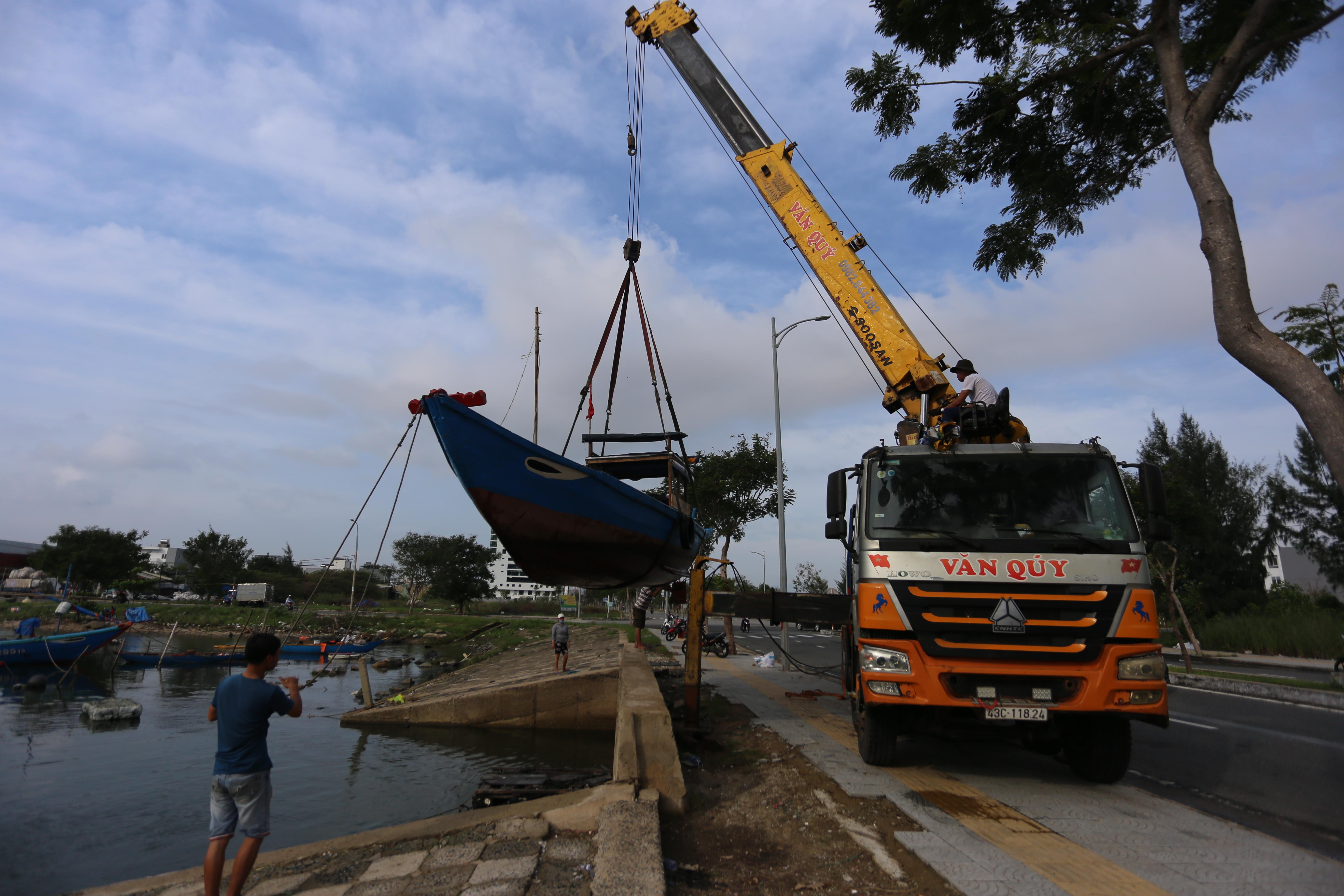 [Ảnh] Xe tải cẩu chở thuyền đến nơi an toàn, công an, bộ đội giúp người Đà Nẵng chằng chống nhà cửa đón bão số 9 - Ảnh 1.