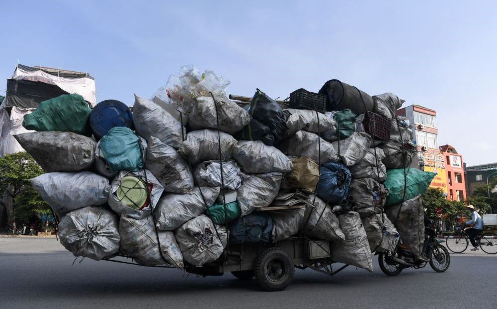 24h qua ảnh: Xe máy kéo xe bò chở rác tái chế trên đường phố ở Hà Nội