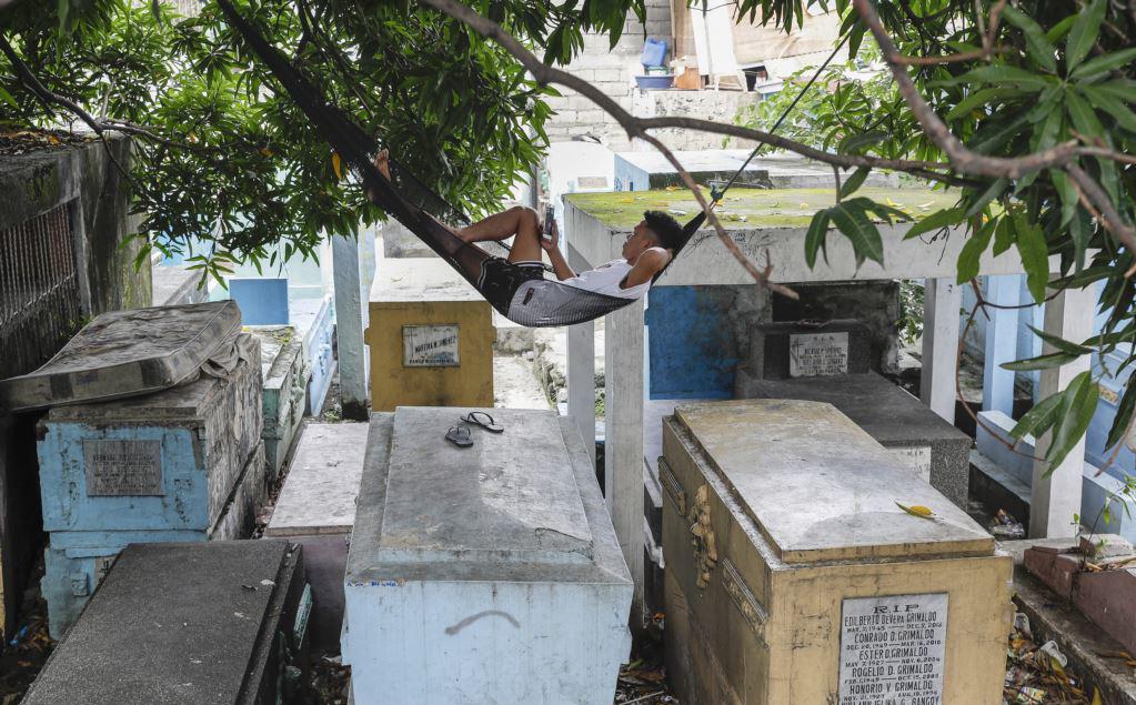24h qua ảnh: Người đàn ông mắc võng nằm nghỉ trong nghĩa địa