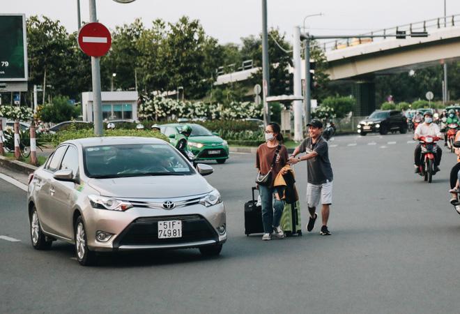 Khổ như hành khách ở Tân Sơn Nhất: Đội nắng mang vác hành lý ra đường đón xe công nghệ - Ảnh 13.