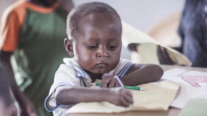 Đang ngồi làm bài tập thì bị chụp ảnh trộm, cậu bé da đen bỗng chốc nổi tiếng cả thế giới, cuộc đời bước sang trang mới - Ảnh 1.
