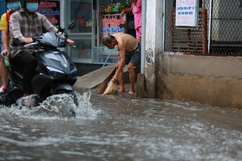 [ẢNH] Nước chảy xiết kéo nhiều xe máy đổ nhào giữa phố Sài Gòn, người dân dắt bộ cho an toàn - Ảnh 11.
