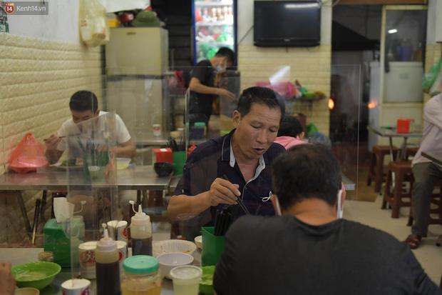 Hà Nội trong ngày đầu tiên giãn cách hàng quán: Bàn được lắp vách ngăn, khách ngồi cách xa nhau hơn 1 mét - Ảnh 12.