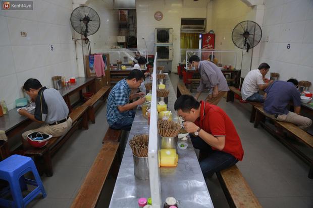 Hà Nội trong ngày đầu tiên giãn cách hàng quán: Bàn được lắp vách ngăn, khách ngồi cách xa nhau hơn 1 mét - Ảnh 11.