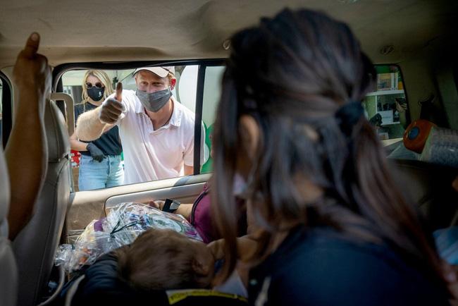 Vợ chồng Meghan Markle xuống đường phát đồ từ thiện nhưng bị mỉa mai vì mang theo nhiếp ảnh gia riêng để chụp ảnh - Ảnh 4.