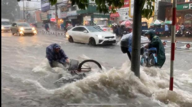 Thót tim cảnh học trò bất chấp đạp xe về nhà giữa lúc mưa bão, bị nước cuốn trôi; cặp sách, xe đạp văng xa cả mét - Ảnh 1.